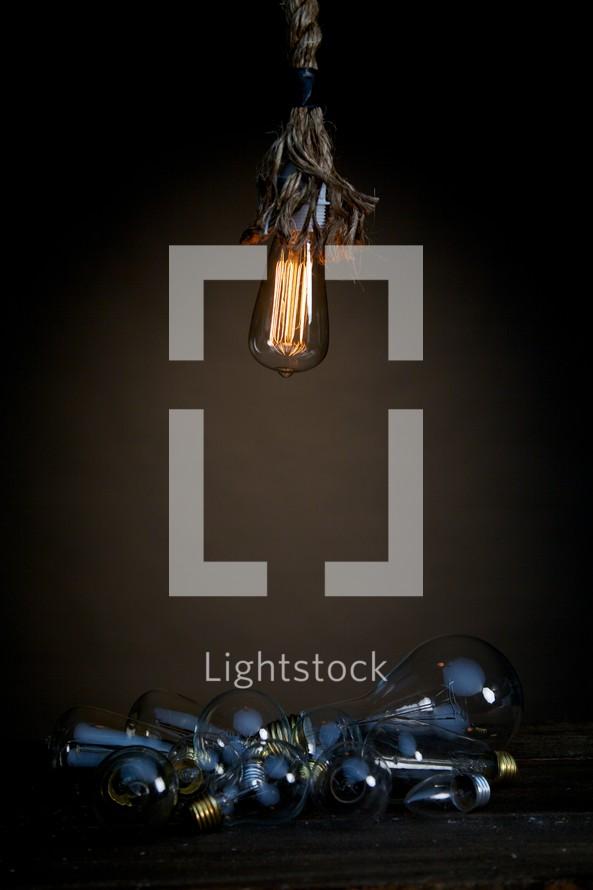 An illuminated lightbulb shining on a pile of unlit bulbs