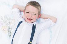 a little boy in suspenders relaxing on a blanket