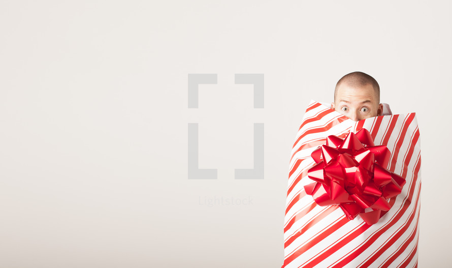 A man covered by wrapping paper and bow