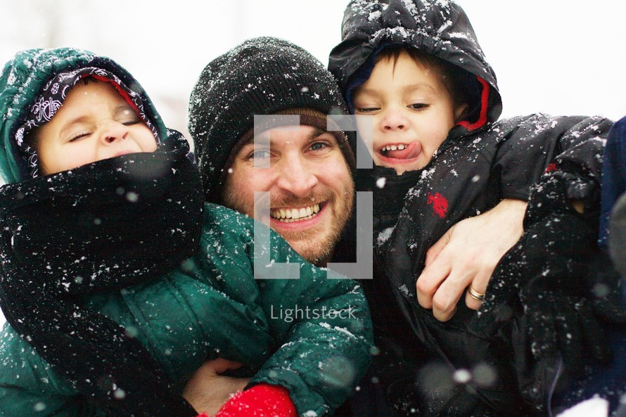 Dad and kids playing in the snow