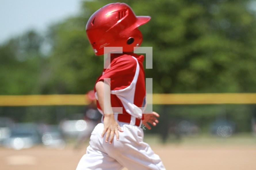 A boy runs for home plate in a little league baseball game