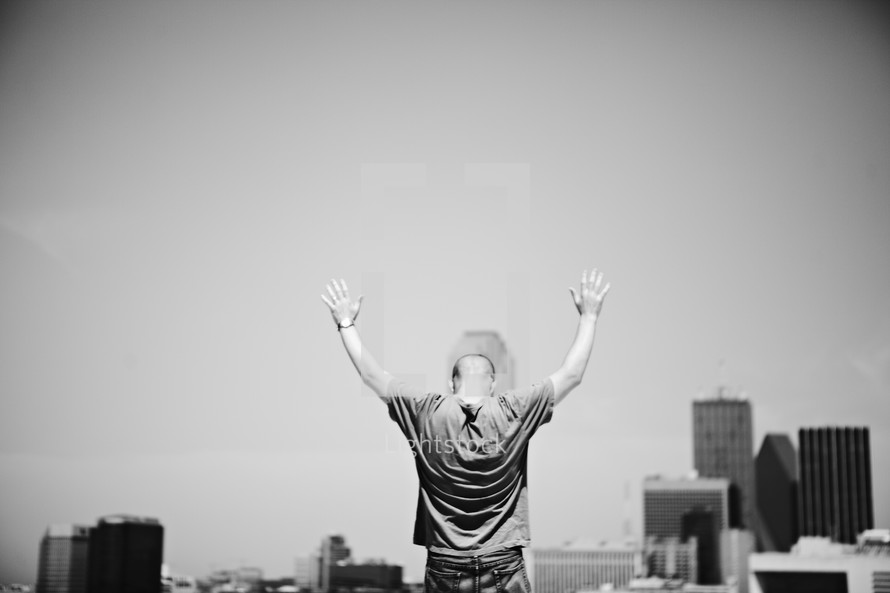 A man with arms raised in prayer over the city