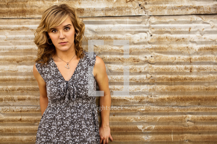 A young woman poses in front of a tin wall