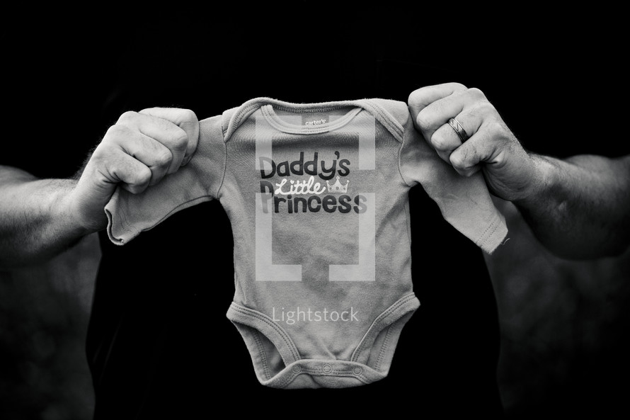 closeup of a father holding a onesie with the words DADDY'S LITTLE PRINCESS