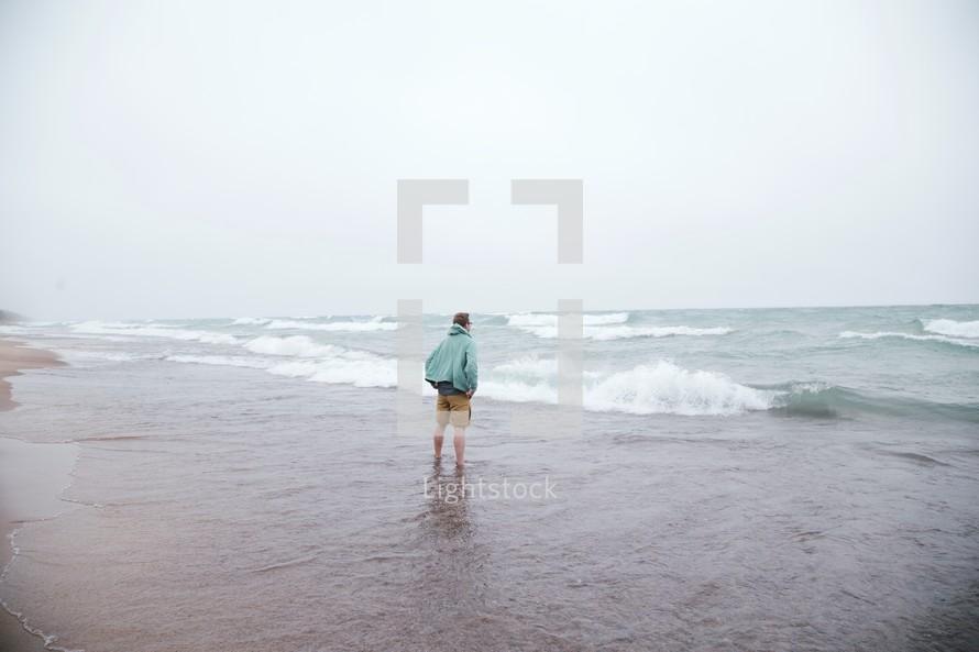man standing in the ocean