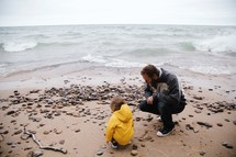 father and son looking at rocks along a shore