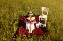 a woman reading a book on a blanket in the grass
