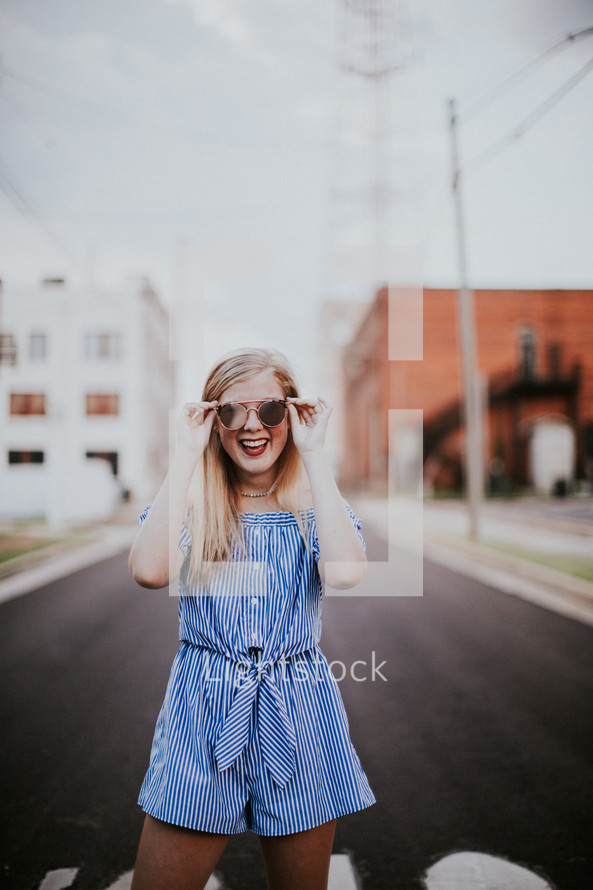 teen girl in a romper standing in the middle of a road