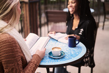women discussing scripture sitting at an outdoor table