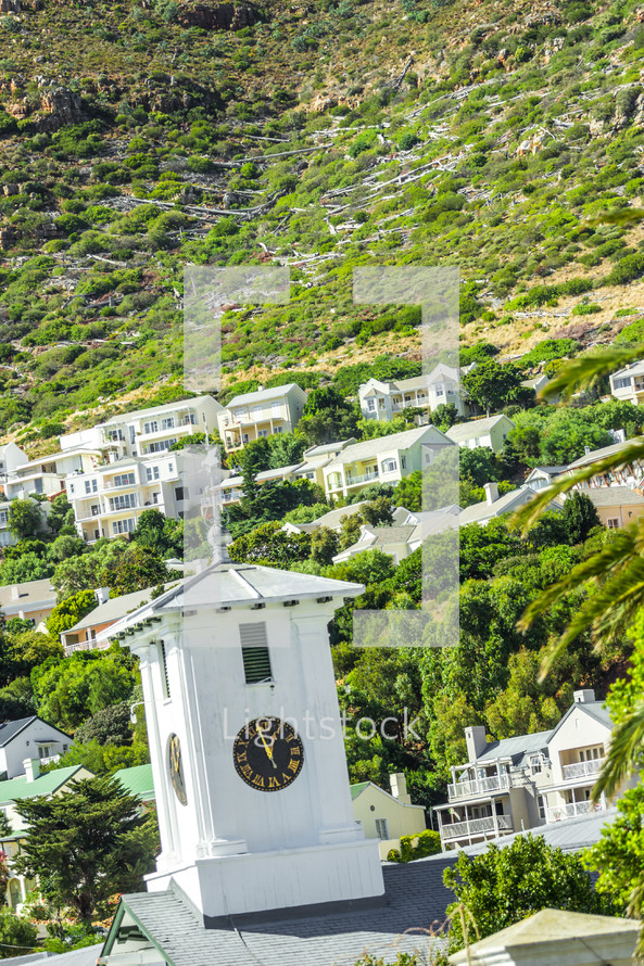Clock tower and homes on a steep hillside.
