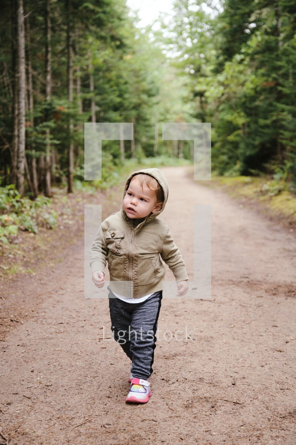 toddler walking on a dirt road