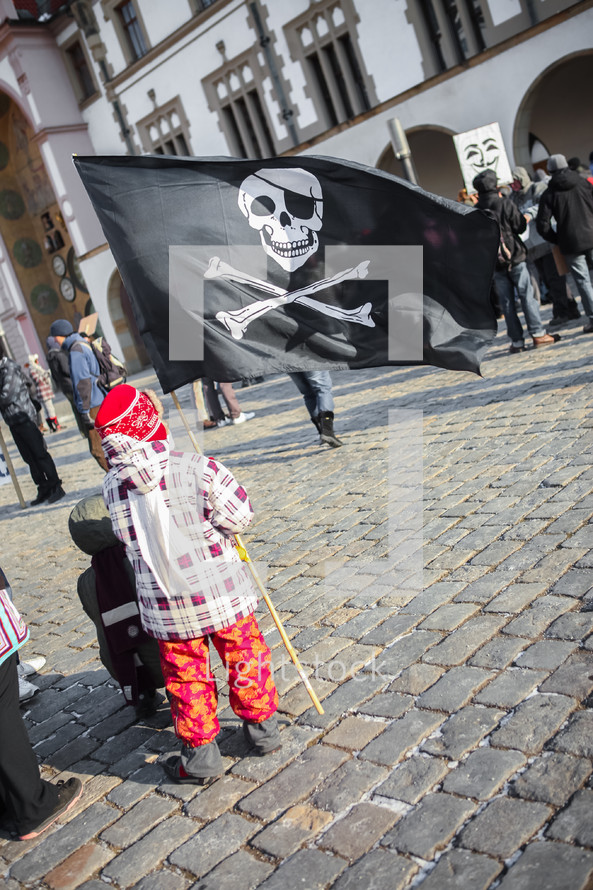 A child holding a pirate skull flag.