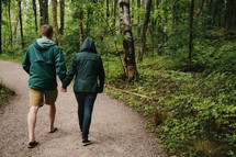 a couple holding hands walking on a nature trail