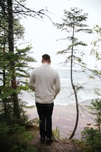 man looking down at a beach watching the tide lap onto a shore