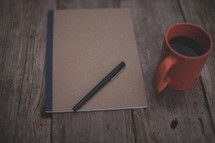 A pen and notebook next to an orange coffee mug