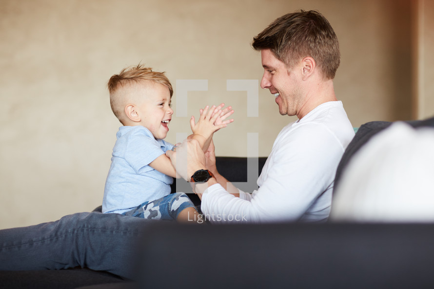 a father holding his son on a couch