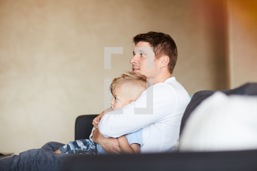 a father hugging his son on the couch
