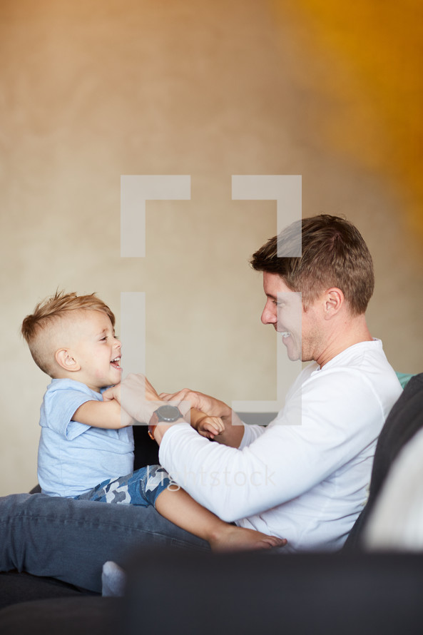 a father playing with his son on a couch