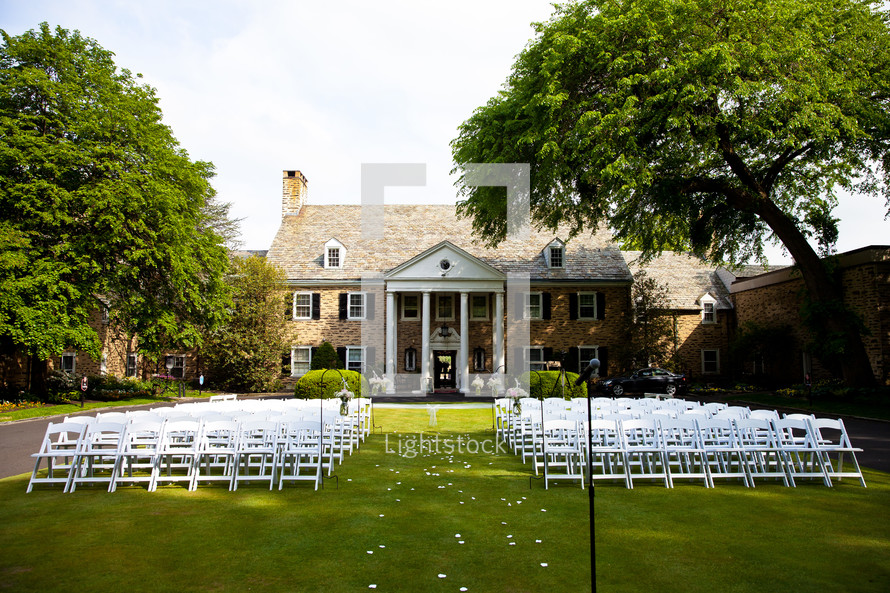 White chairs set up on a green lawn for a wedding.