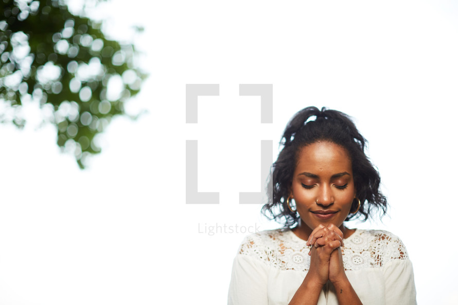 a woman with praying hands outdoors