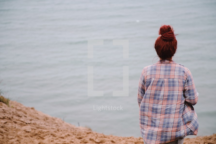 a woman sitting on a lake shore looking out a the water