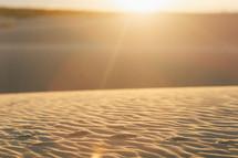 sunlight shining on ripples in sand