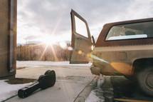 guitar on a sidewalk behind an SUV
