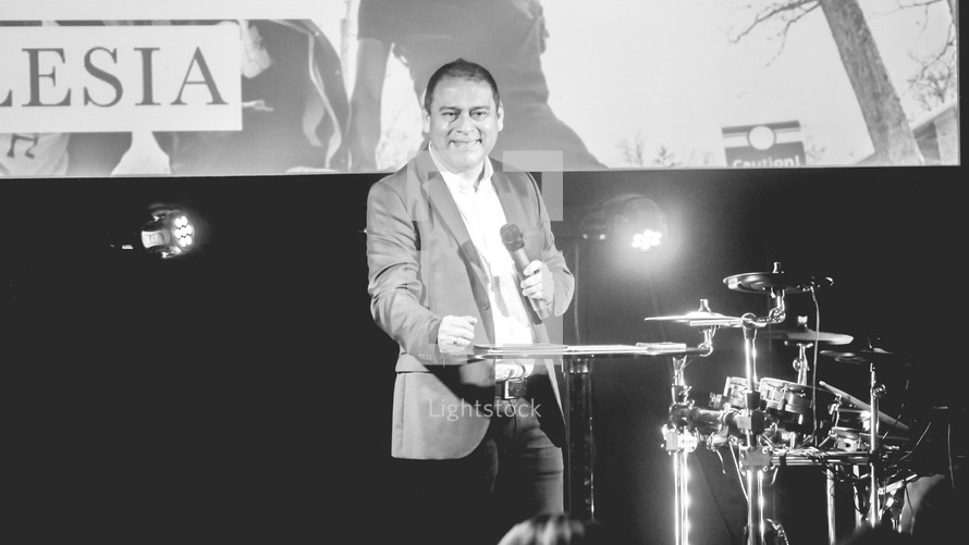 a minister holding a microphone on stage during a worship service