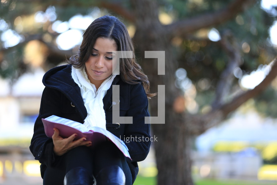 Woman sitting in front of large tree reading Bible.