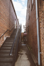 Stairway in an alley between two brick buildings.