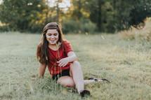 teen girl sitting in a field of grass