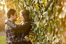a couple looking into each others eyes standing against an ivy covered wall