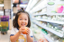 a little girl sitting in a shopping cart holding an orange