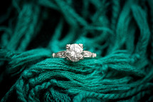 engagement ring on a turquoise scarf