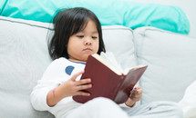 a child reading a book on a couch