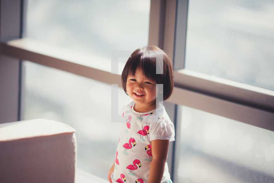 toddler girl standing in front of a window