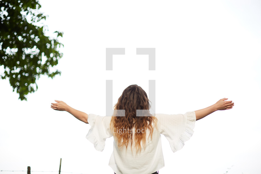 a woman standing outdoors with outstretched arms