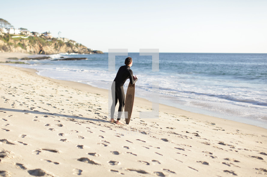 Surfer holding surfboard in the beach sand