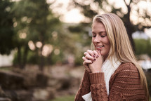 a woman praying outdoors in a sweater