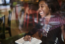 African American woman reading a Bible sitting in a coffee shop window seat