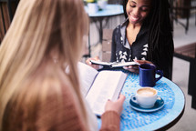 women reading scripture sitting at an outdoor cafe table
