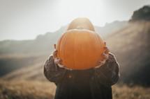 a woman holding up an orange pumpkin