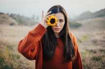 a woman holding a yellow sunflower