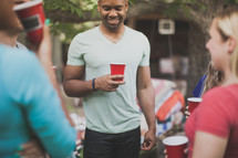 friends holding cups and in conversation at a cookout