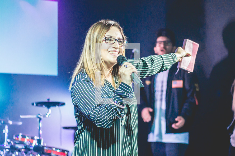 a woman holding a microphone and Bible