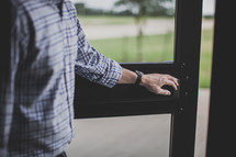 man holding open the door of a church
