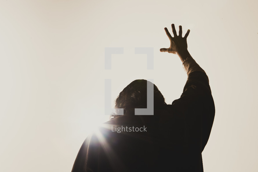 Jesus' hand raised high in the air as the sun shines down on him