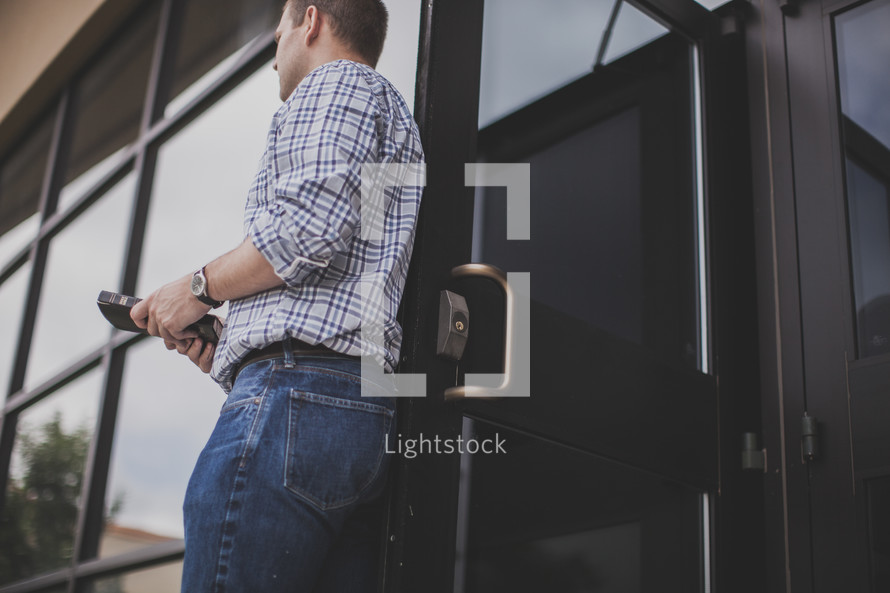 man greeter holding the door open at a church entrance
