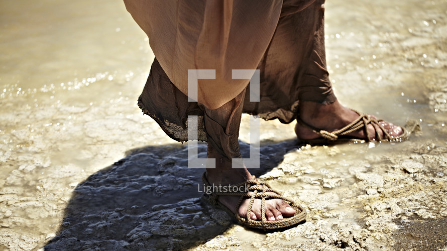 Jesus standing near the water with his feet in sandals.
