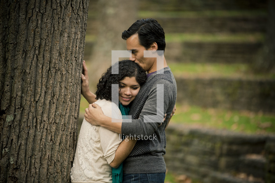 Man kissing woman on top of the head as they lean against a tree.